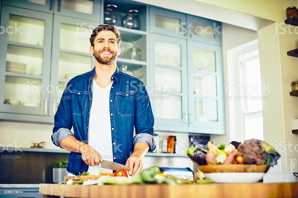 Male looking away while cutting vegetables at kitchen island stock photo