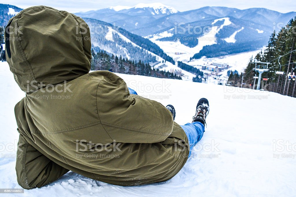 Male lying on snow. Recreation in Carpathian mountains. stock photo
