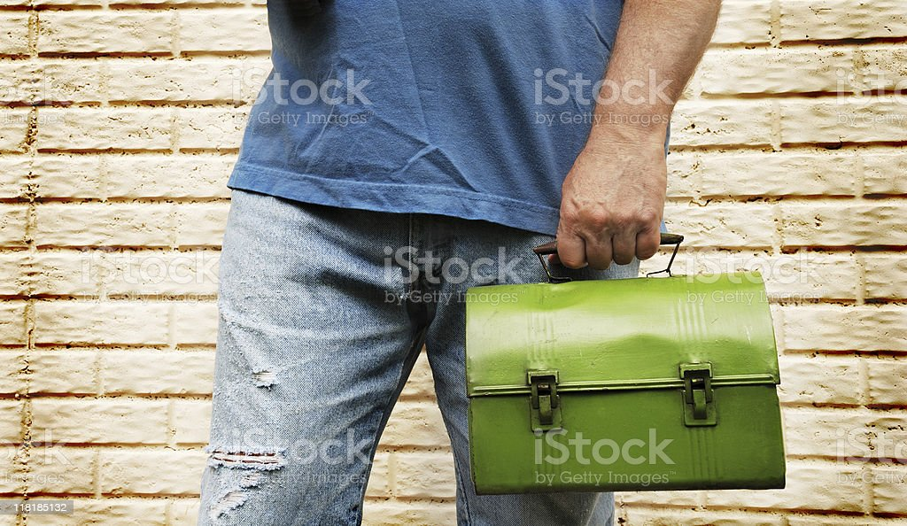 Male manual laborer worker in ripped jeans with lunch box royalty-free stock photo