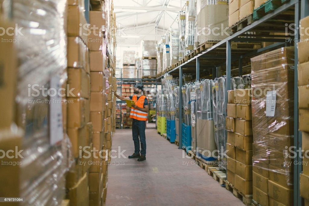 Male manual worker in warehouse checking merchandise stock photo