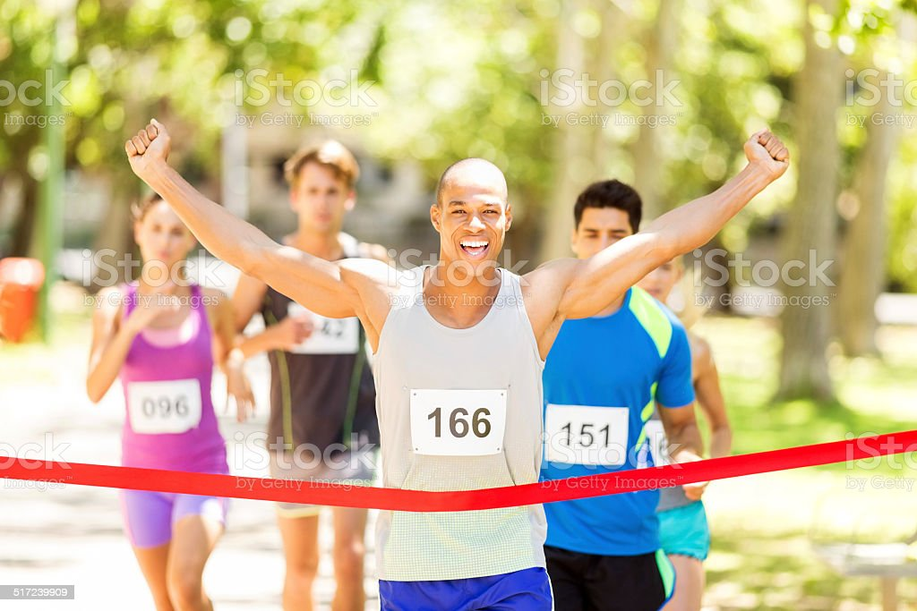 Male Marathon Runner Crossing Finishing Line stock photo