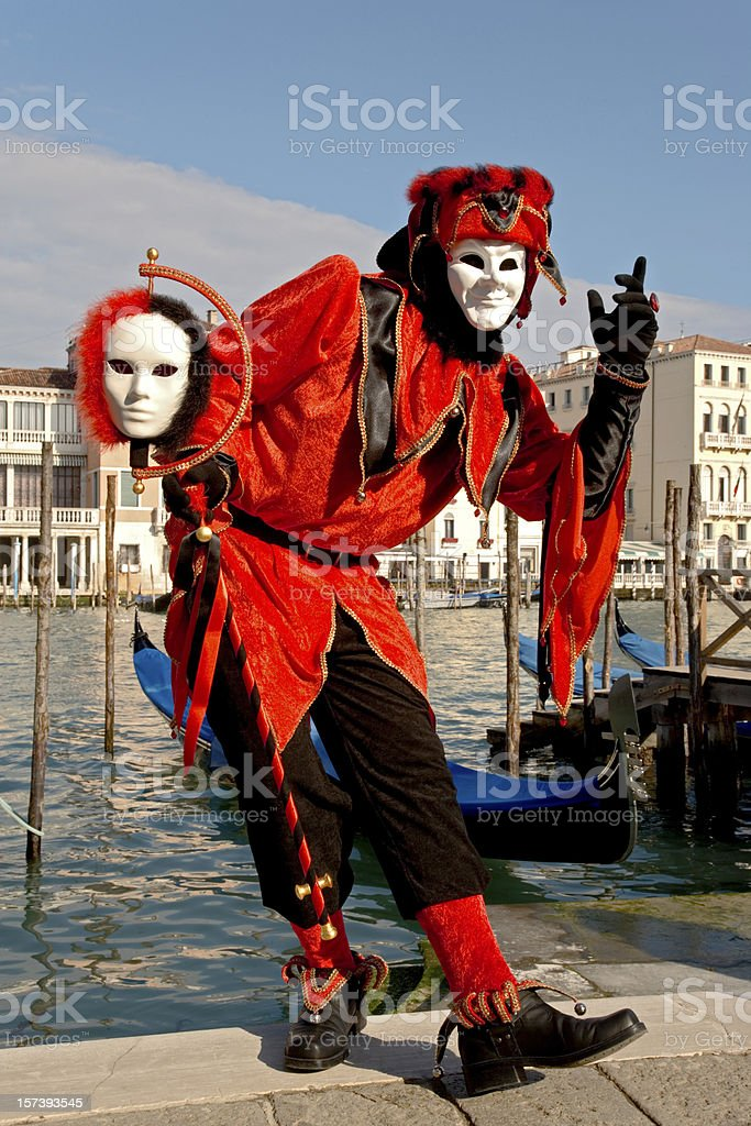 Male mask with red harlequin costume at carnival in Venice stock photo