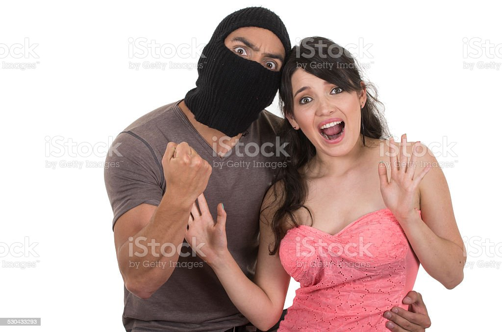 male masked thief holding young girl stock photo