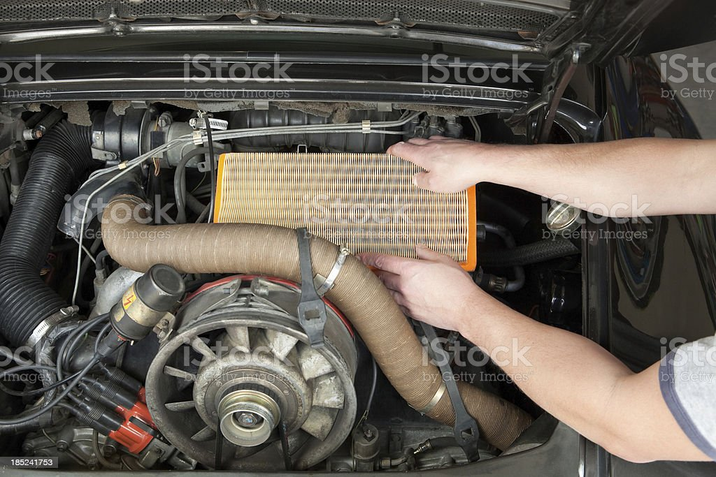 Male Mechanic Hands Installing a New Air Filter royalty-free stock photo