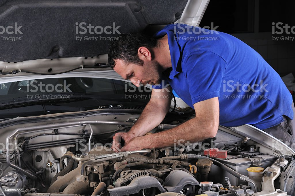 Male mechanic in blue polo shirt working on a car engine royalty-free stock photo