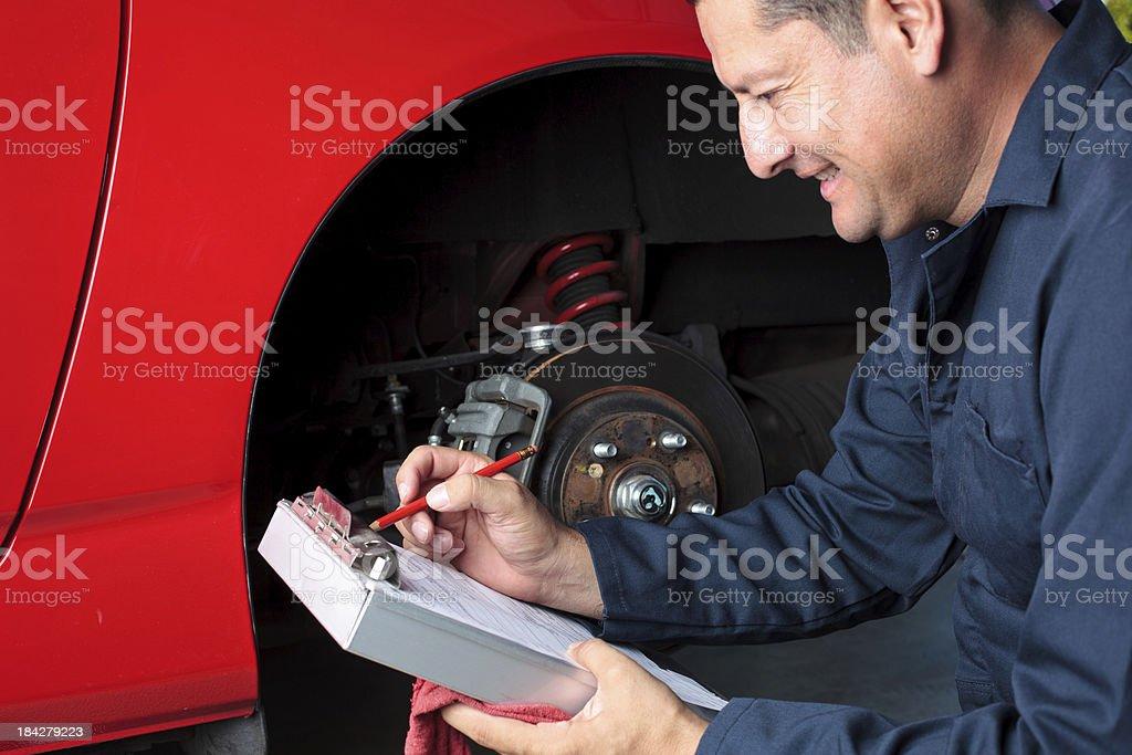 Male mechanic inspecting car breaks royalty-free stock photo