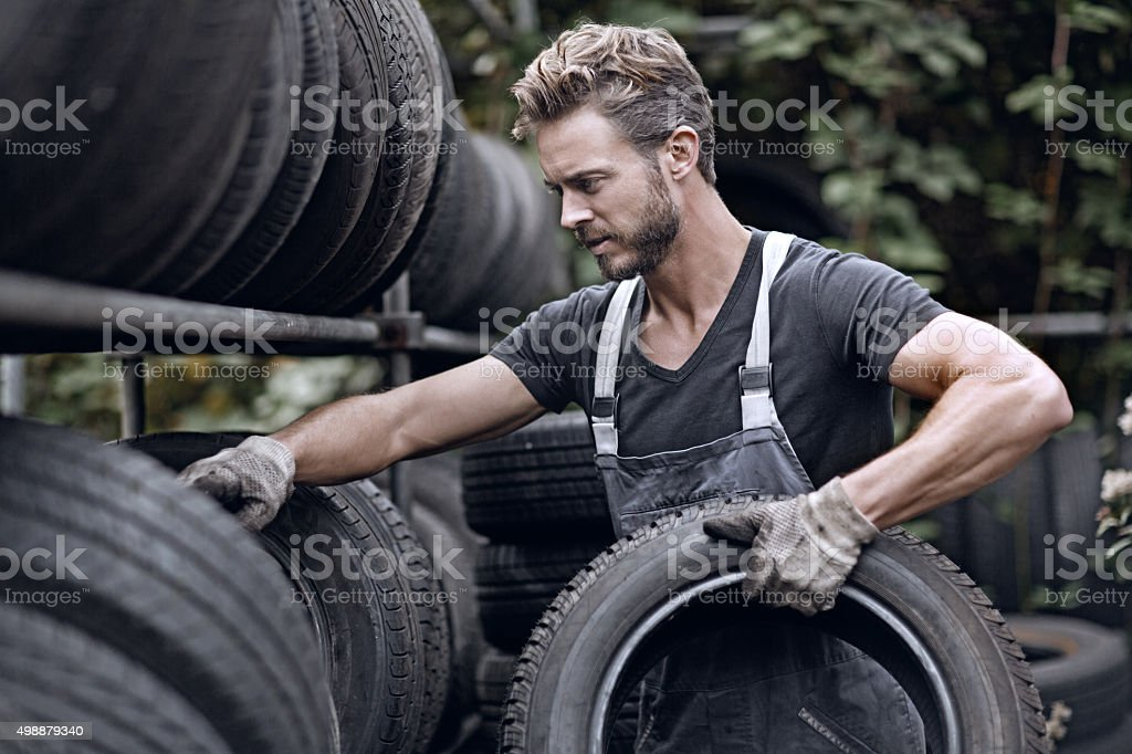 Male mechanic picking up tires stock photo
