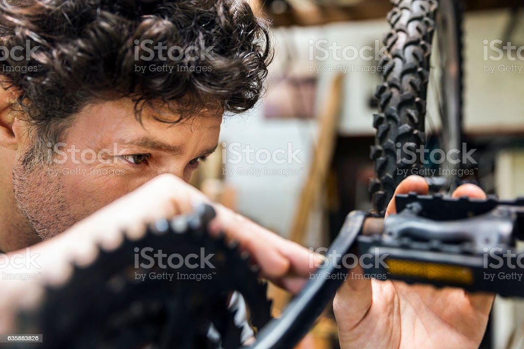Male mechanic repairing bicycle in workshop stock photo