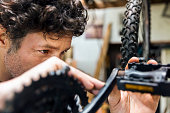 Male mechanic repairing bicycle in workshop