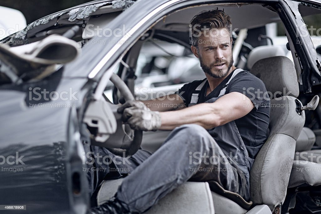 Male mechanic sitting inside broken car stock photo