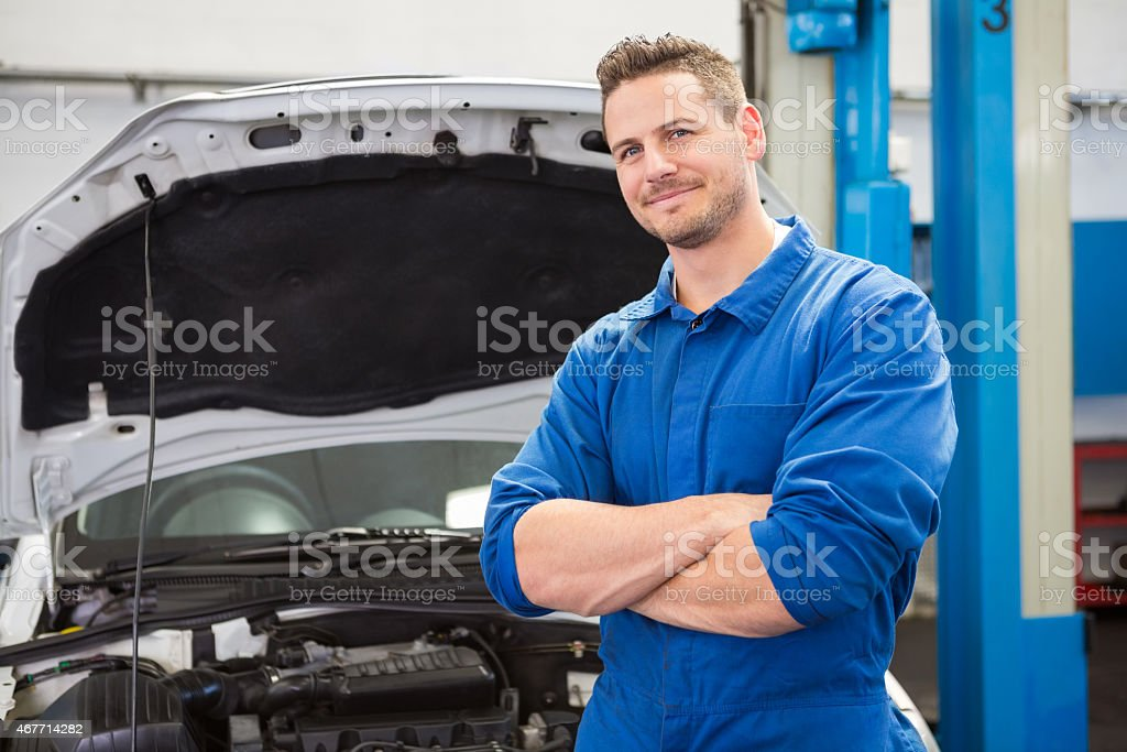 A male mechanic standing by a car and smiling at the camera stock photo
