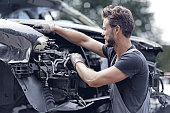 Male mechanic working on destroyed car