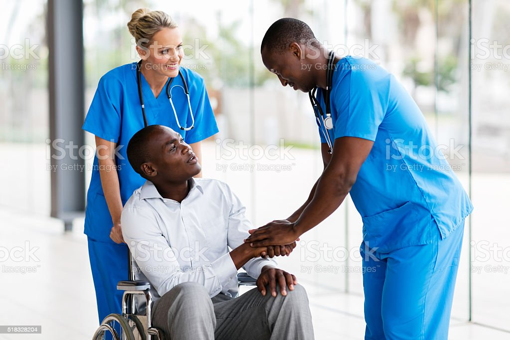 male medical doctor handshaking with handicapped patient stock photo