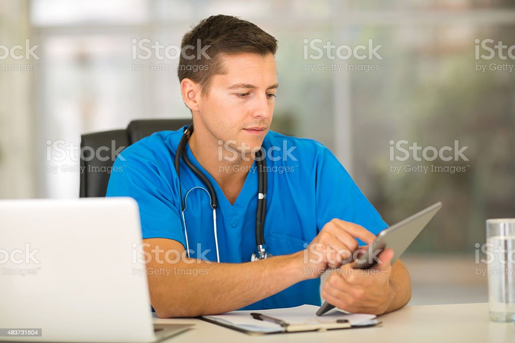 male medical intern using tablet computer stock photo