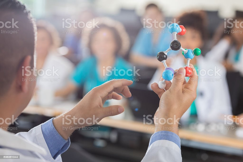 Male medical school professor teaches students about molecular structure stock photo