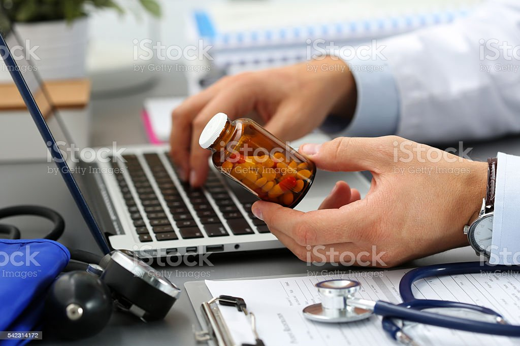 Male medicine doctor hands hold jar of pills stock photo