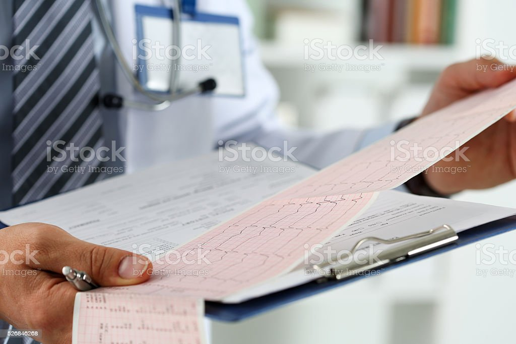Male medicine doctor hands holding cardiogram chart stock photo
