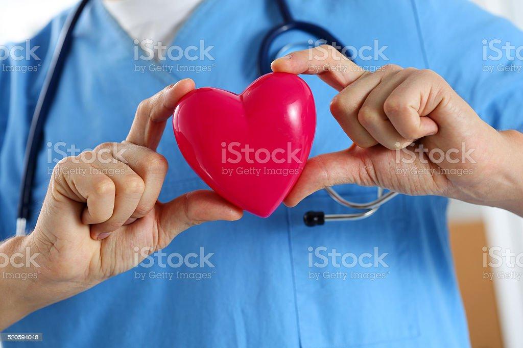 Male medicine doctor wearing blue uniform hold heart stock photo