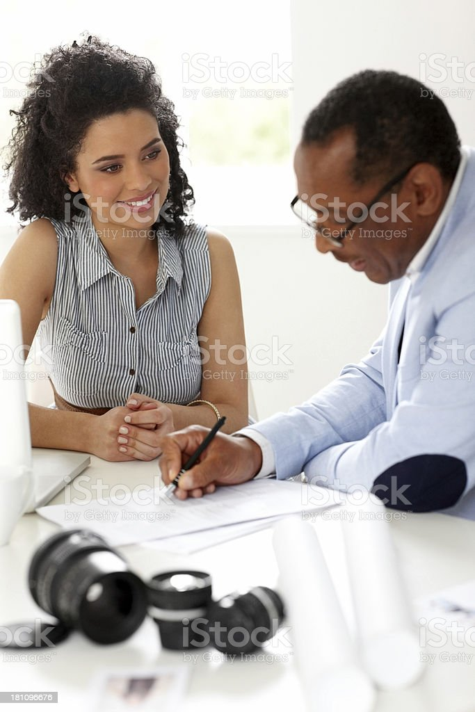 Male mentor teaching his student to fill contract form royalty-free stock photo