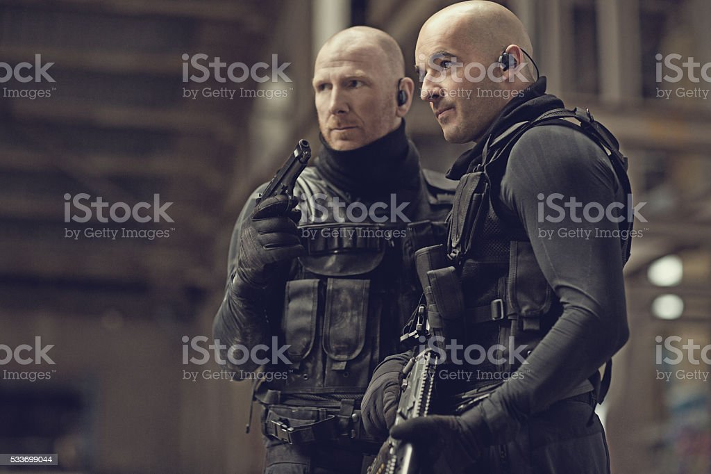 Male military swat team members holding weapons in abandoned warehouse stock photo