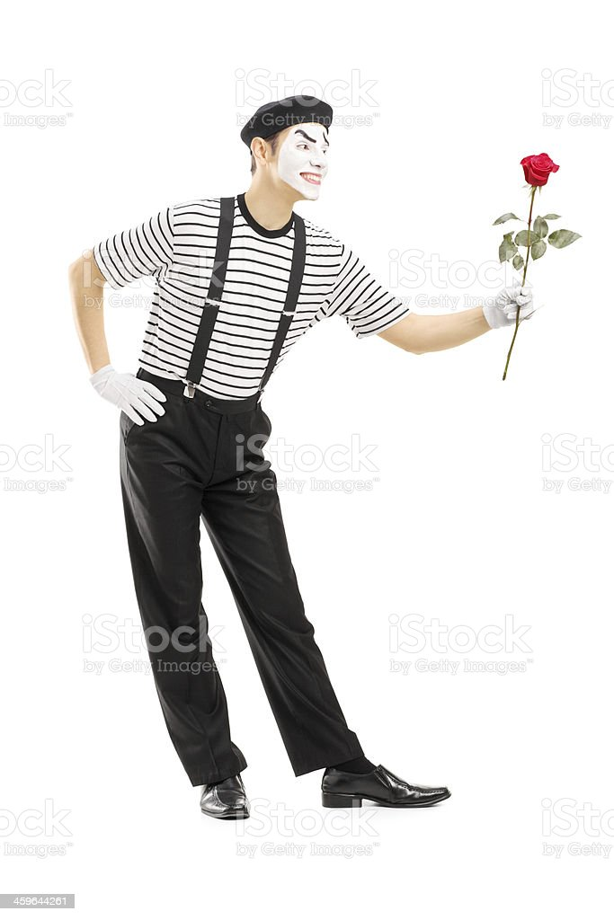 Male mime artist giving a rose flower stock photo