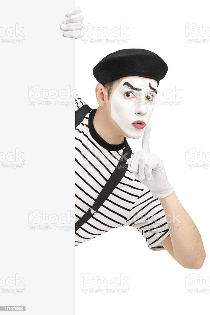 Male mime artist holding a panel and gesturing silence stock photo