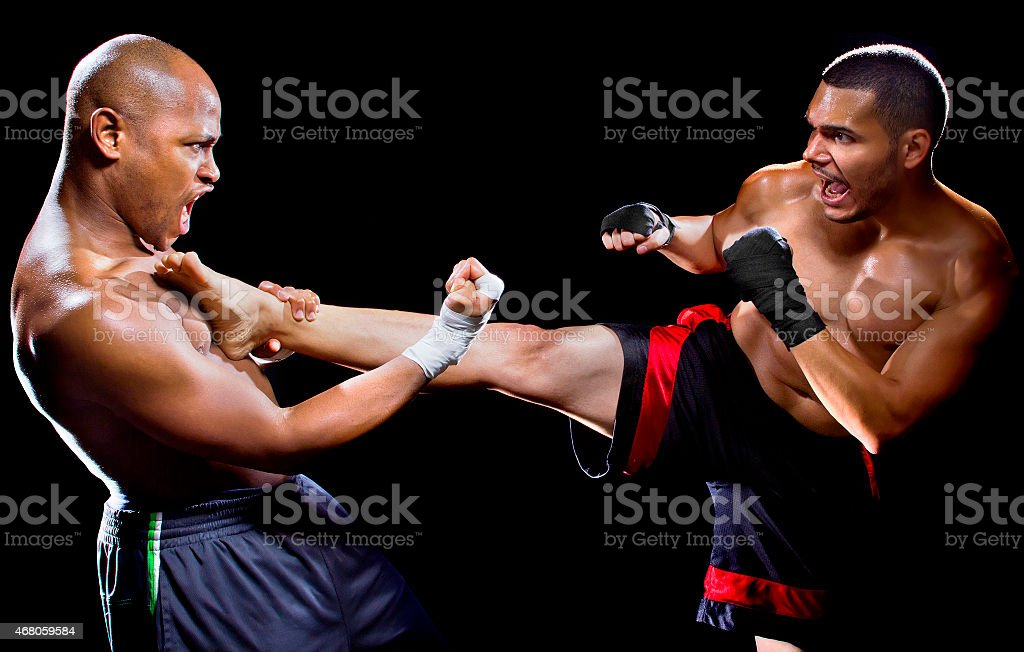 Male MMA Fighter Countering or Blocking a Kick stock photo