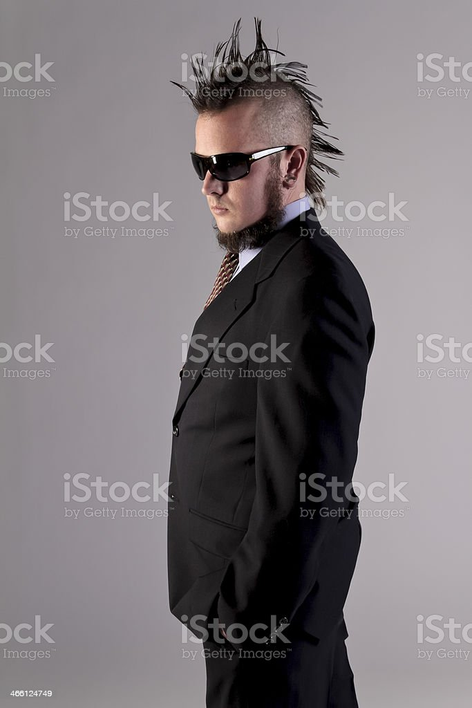 A non-comformist man with a mohawk and beard posing in sunglasses and...