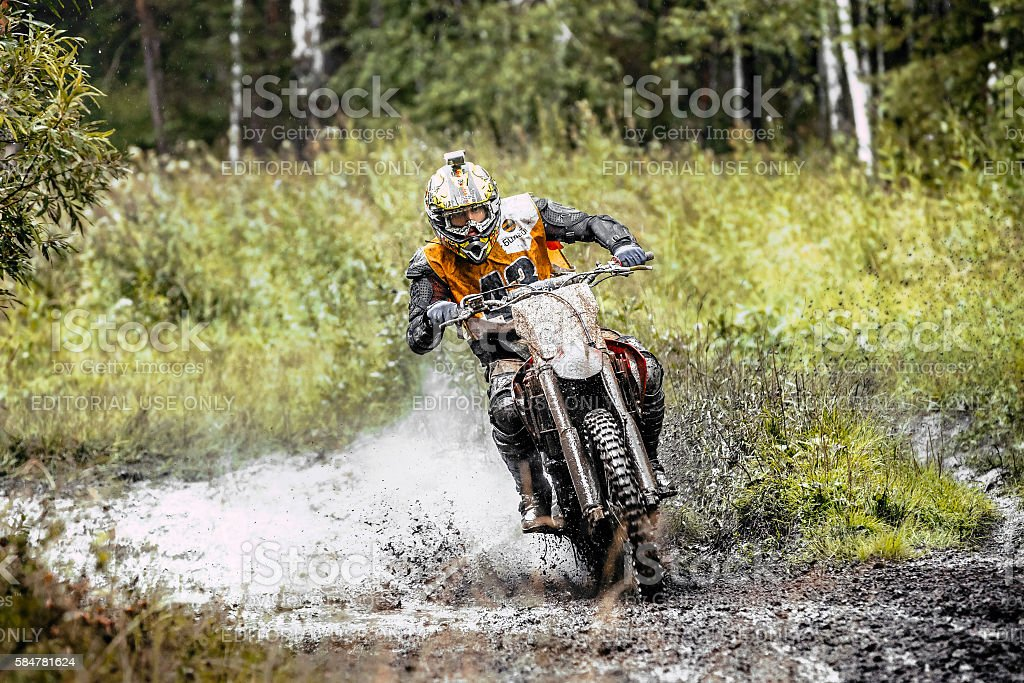 male motorcyclist rides through a puddle of mud in forest royalty-free 스톡 사진