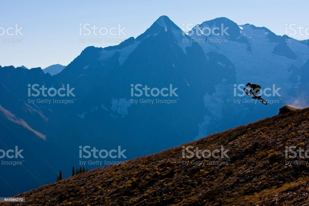 A male mountain bike rider hits a jump on a downhill trail at the end of the day. stock photo