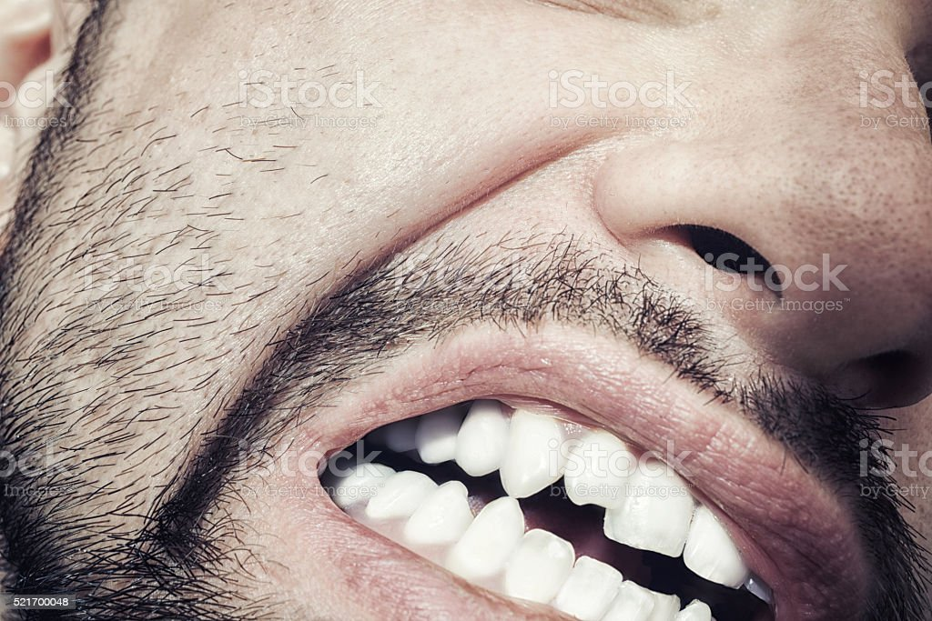 Male mouth with bared teeth close-up stock photo