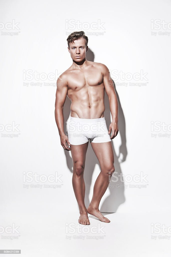 Male muscled underwear model wearing white shorts. Blonde hair. stock photo
