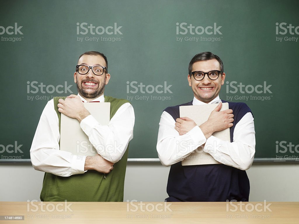 Male nerds holding books tight. royalty-free stock photo