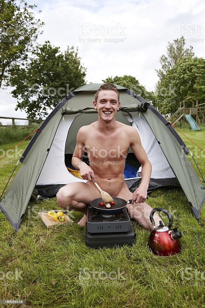 Male nudist cooking sausages on camping stove stock photo