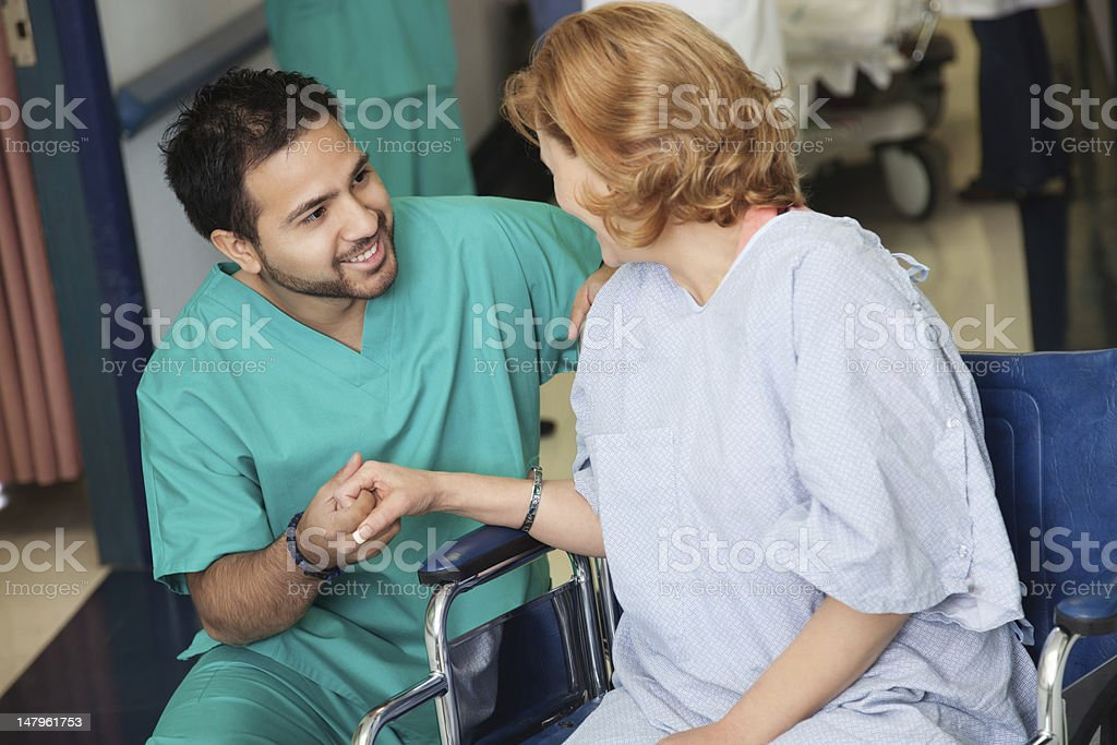 Male nurse assisting wheelchair patient in hospital royalty-free stock photo