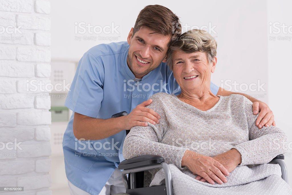 Male nurse hugging his senior woman patient stock photo