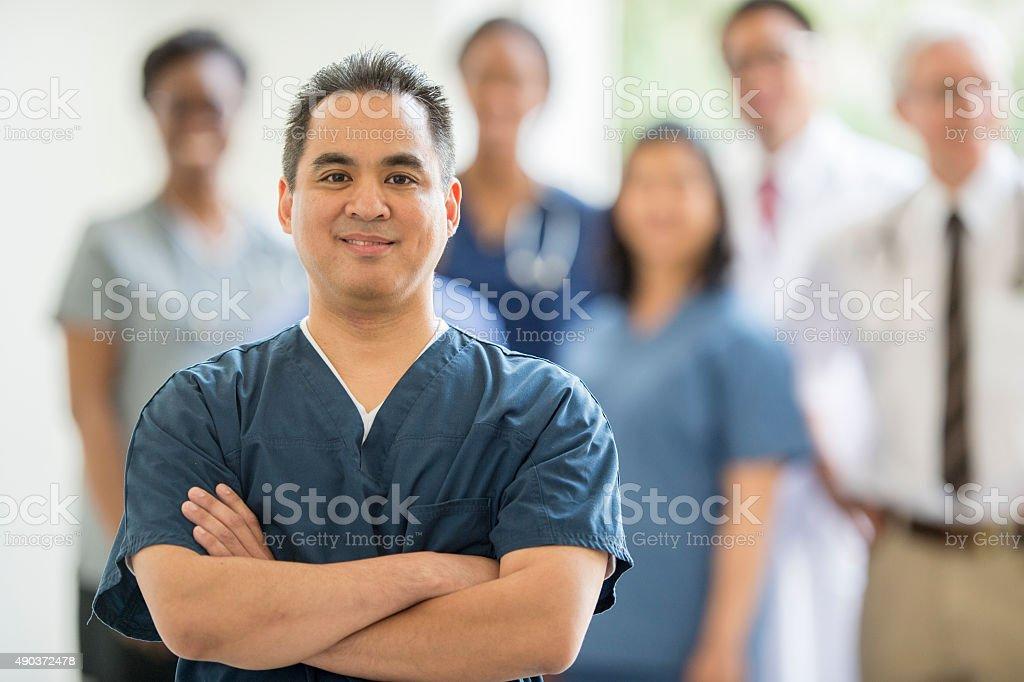 Male Nurse Standing with Associates stock photo