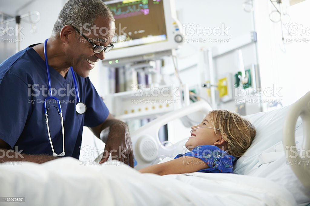 Male nurse talking to child in hospital bed stock photo