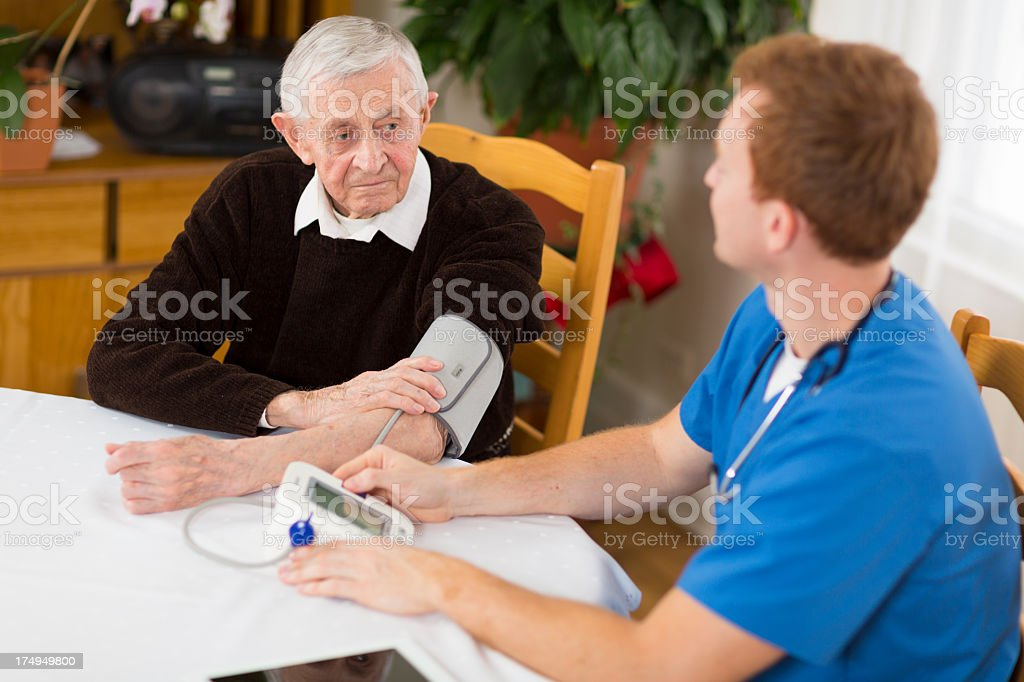 Male nurse visiting a patient at home stock photo
