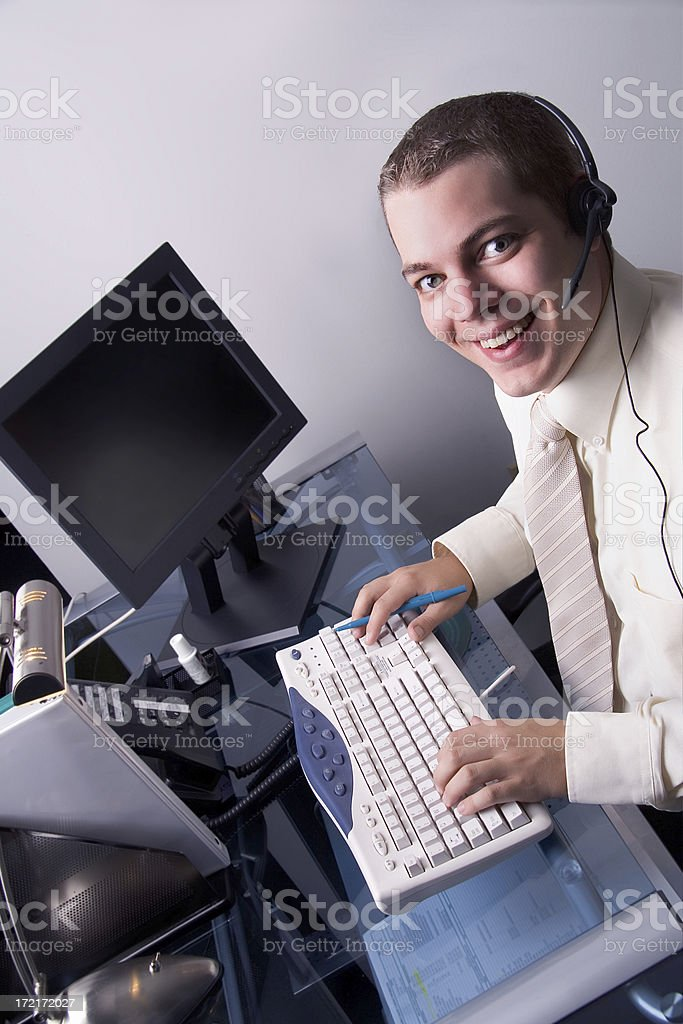 Male office worker at desk with headset royalty-free stock photo