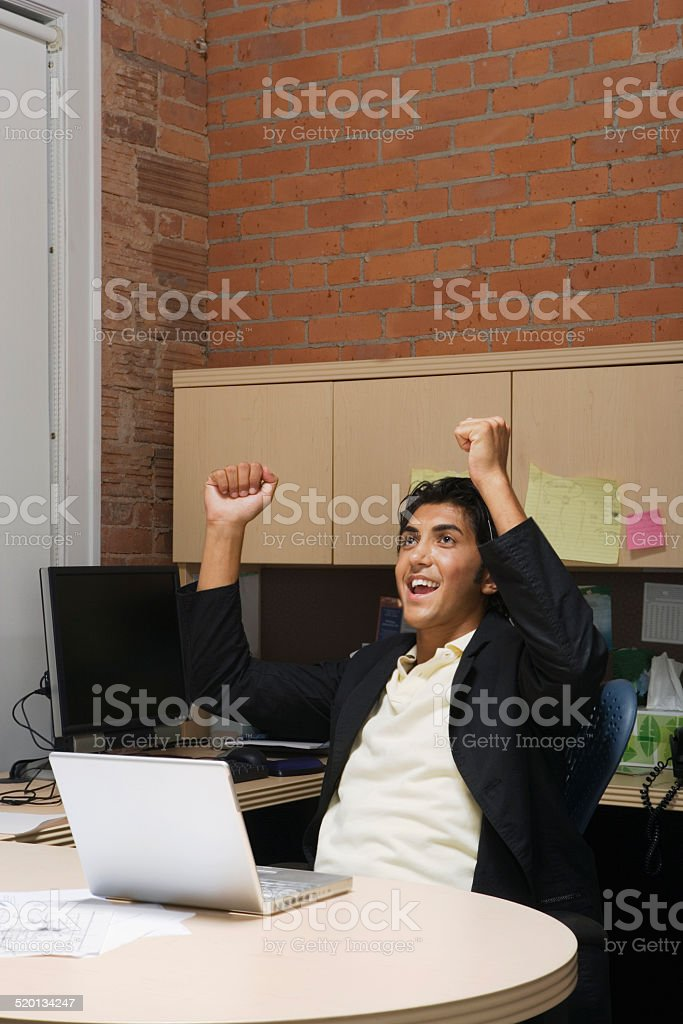 Male office worker cheering at desk stock photo