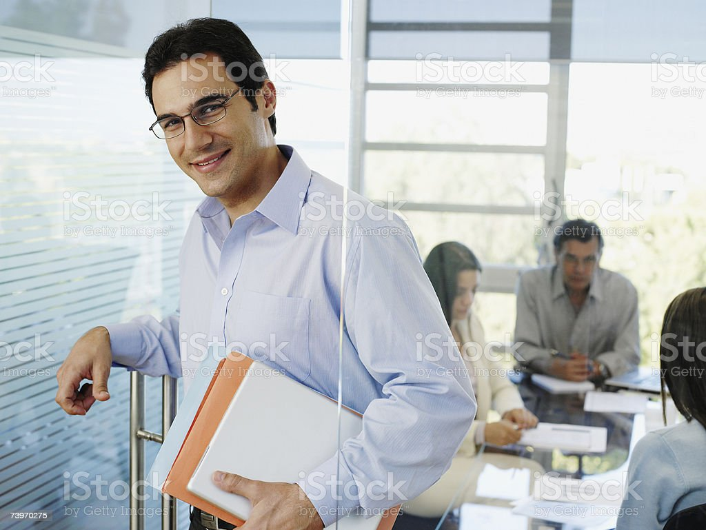 Male office worker holding papers while colleagues meet in background royalty-free stock photo