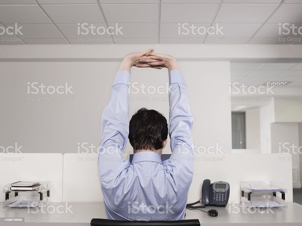Male Office Worker Stretching At Desk stock photo