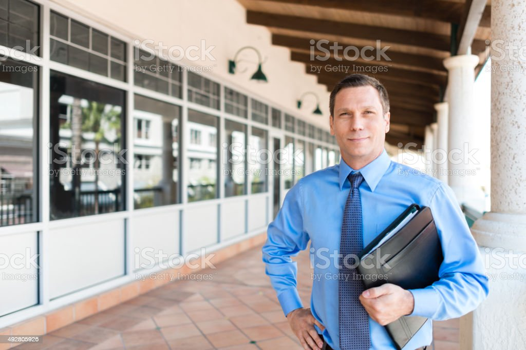 Male office worker with arms crossed stock photo