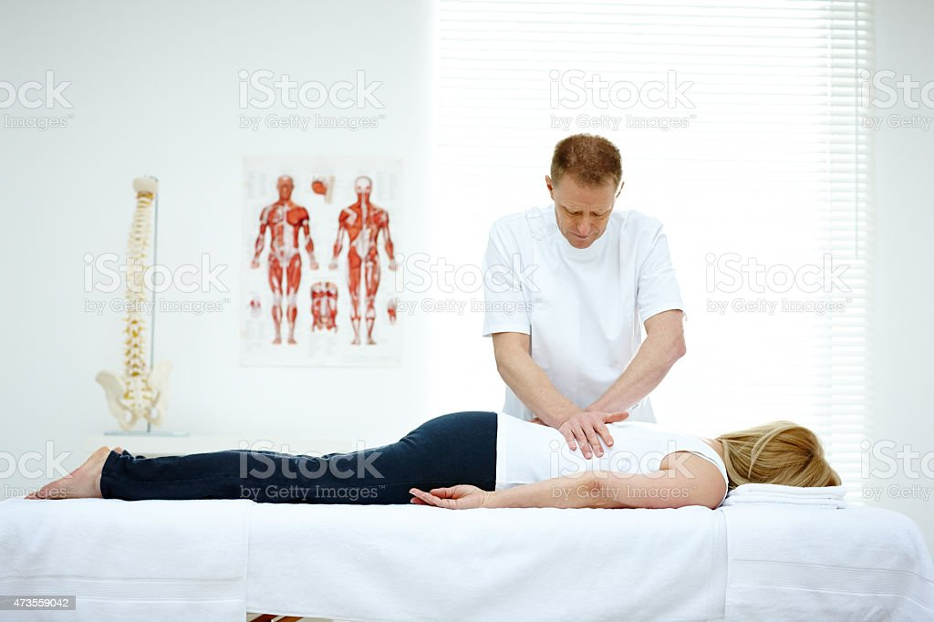 Male osteopath treating back problem of a woman stock photo