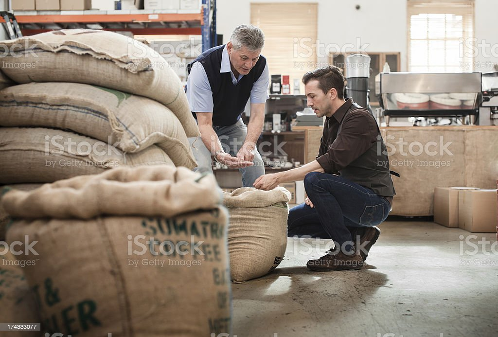 Male owner of a coffee roasting business talking with worker stock photo
