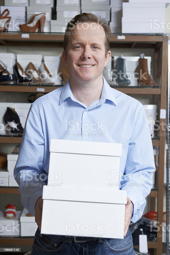Male Owner Of Shoe Store Carrying Boxes royalty-free stock photo