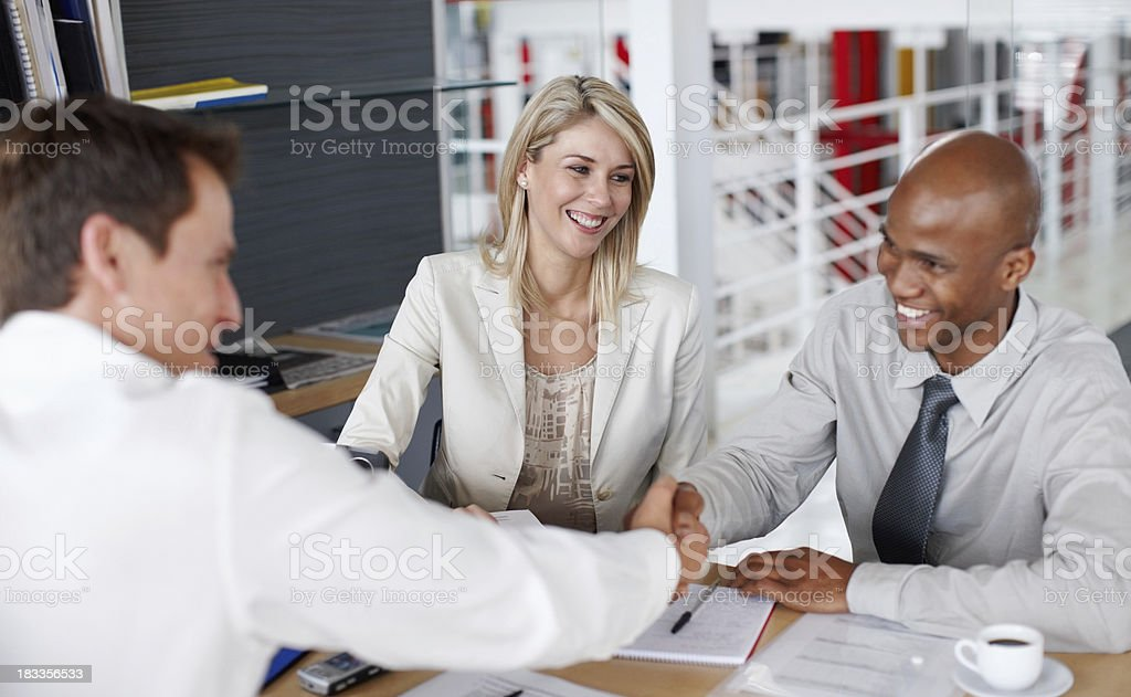 Male partners shaking hands after a business deal at desk royalty-free stock photo