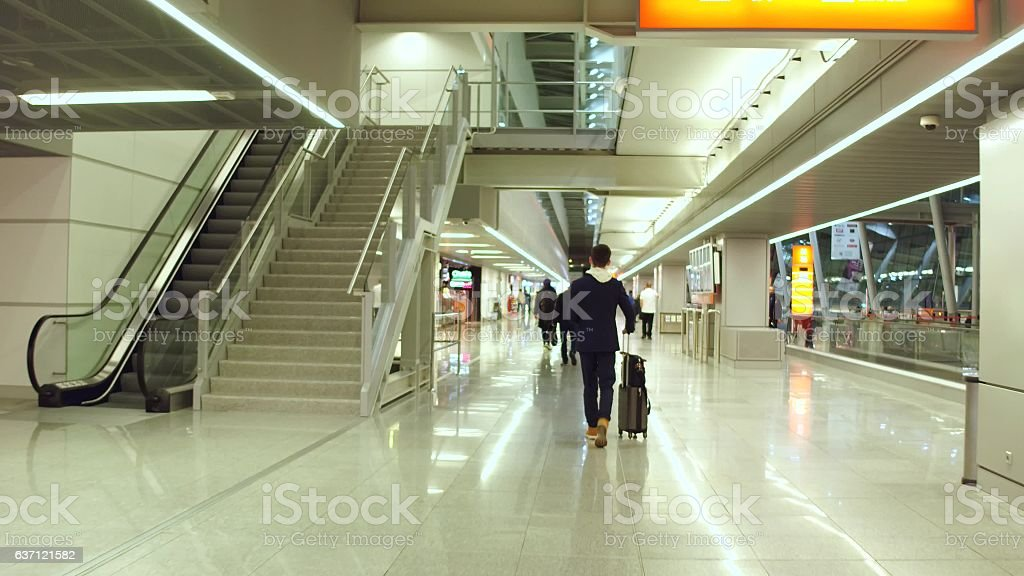 Male passenger with suitcase at international airport terminal stock photo