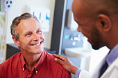 Male Patient Being Reassured By Doctor In Hospital Room